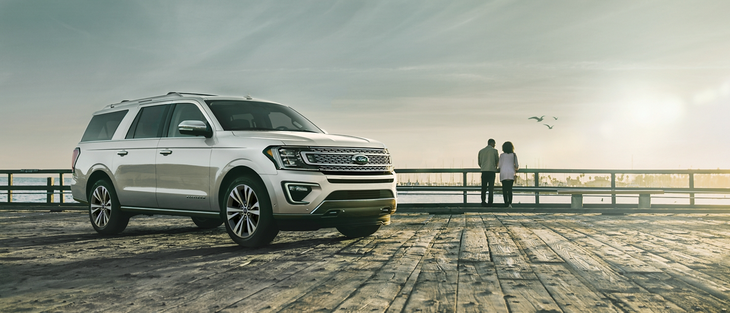 2020 Ford Expedition Platinum with distinctive five bar grille on a dock by a lake