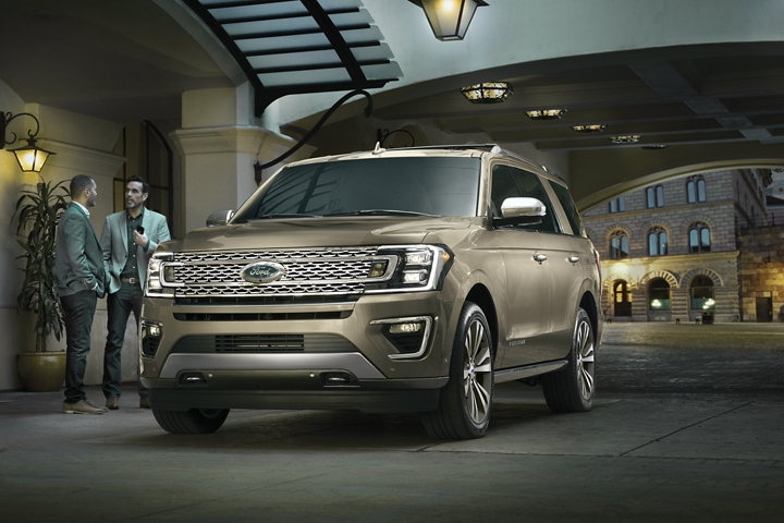 2020 Ford Expedition Platinum in Desert Gold parked in the city by two men talking
