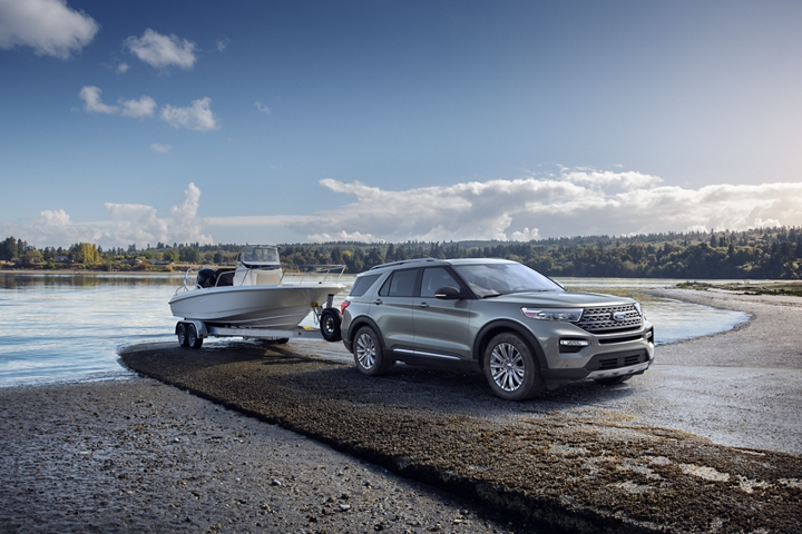 A 2020 Explorer in Silver Spruce towing a boat near a lake
