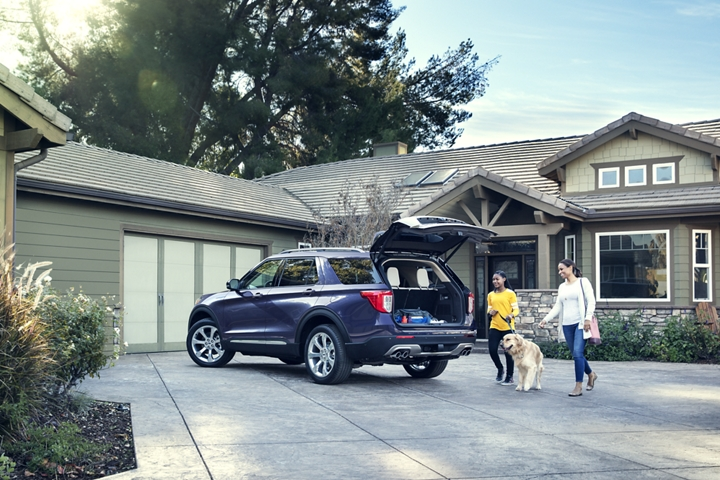 A mom and daughter walk their dog toward a 2020 Explorer