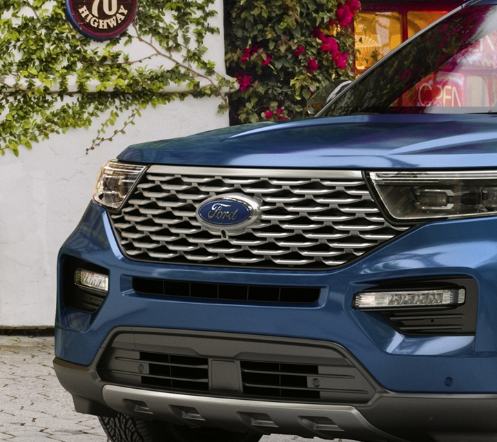 Explorer Platinum in atlas blue in front of a store covered in shrubbery