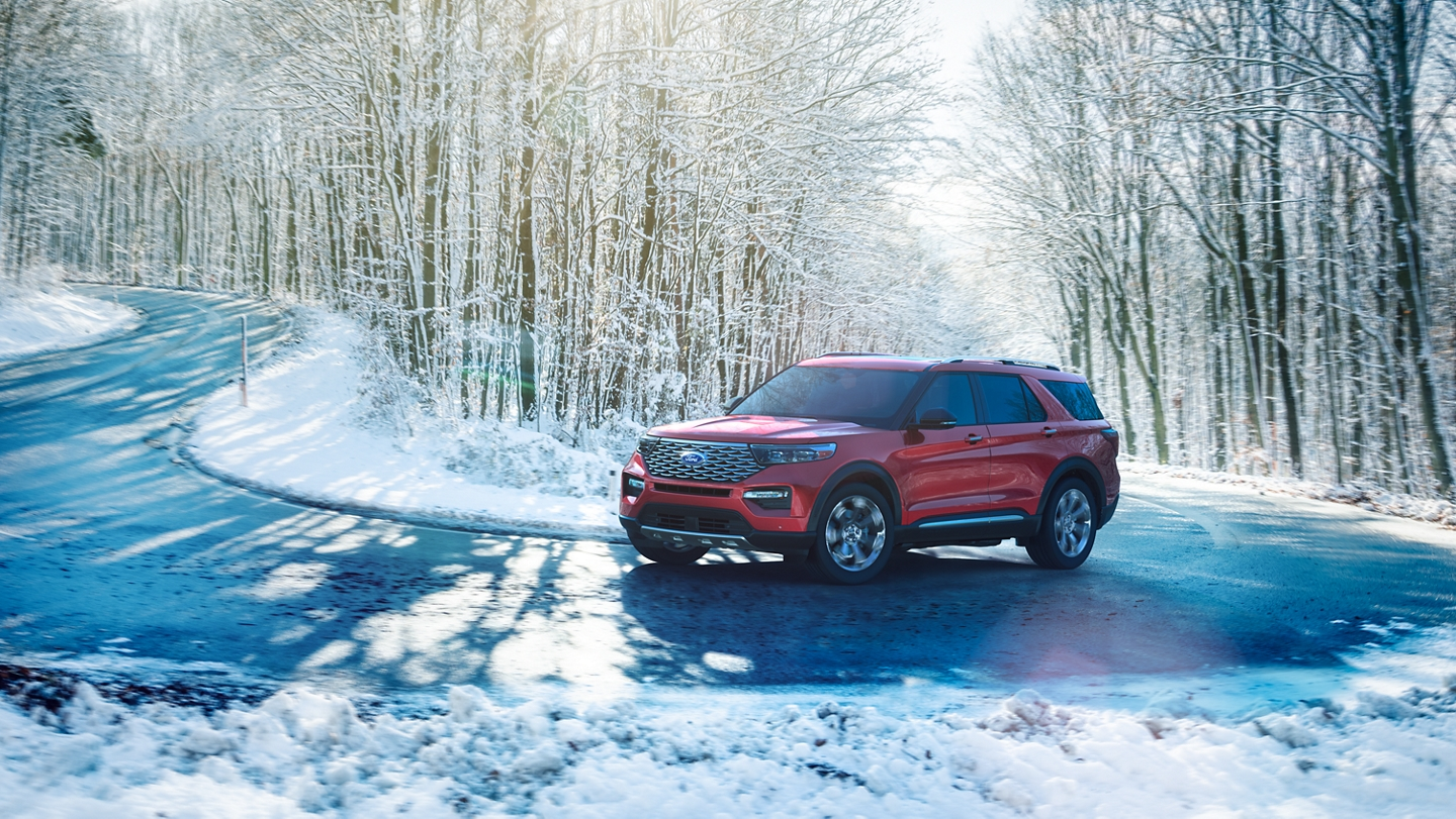 2020 Ford Explorer in rapid red driving on a snowy road