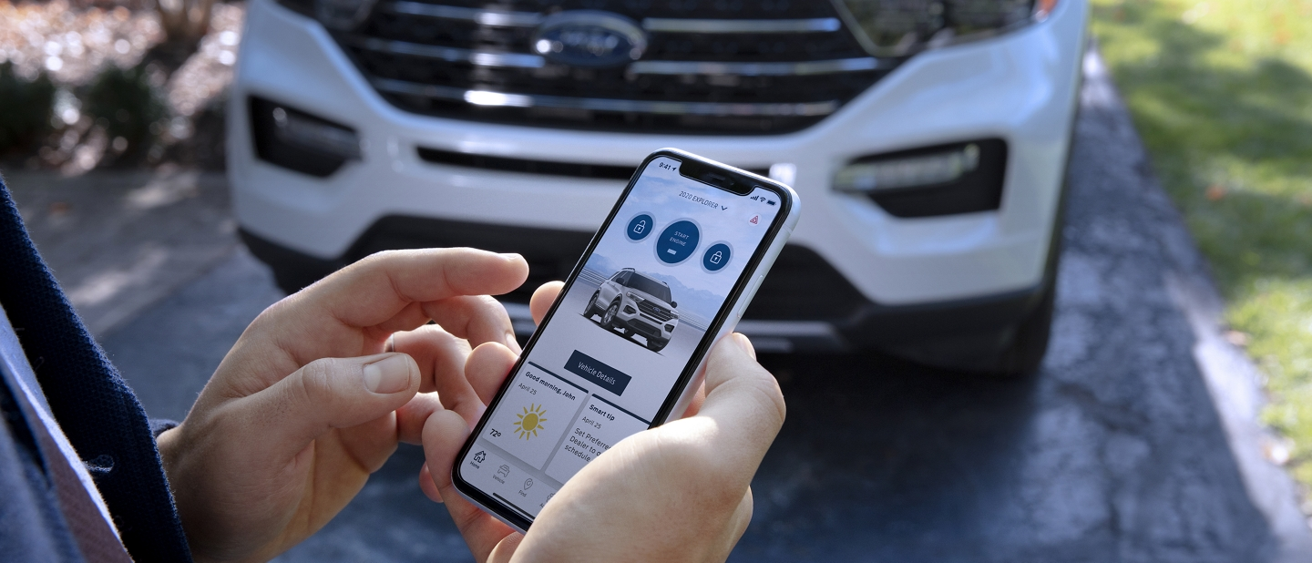 A man stands in front of a white Ford Explorer holding a smartphone displaying the FordPass App