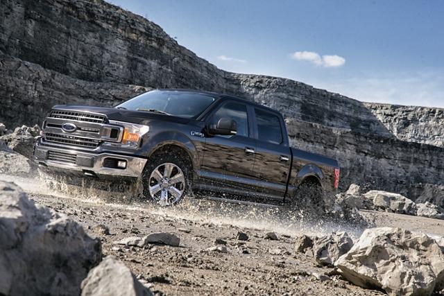 Una Ford F 1 50 2020 subiendo una colina en un lugar todo terreno remoto