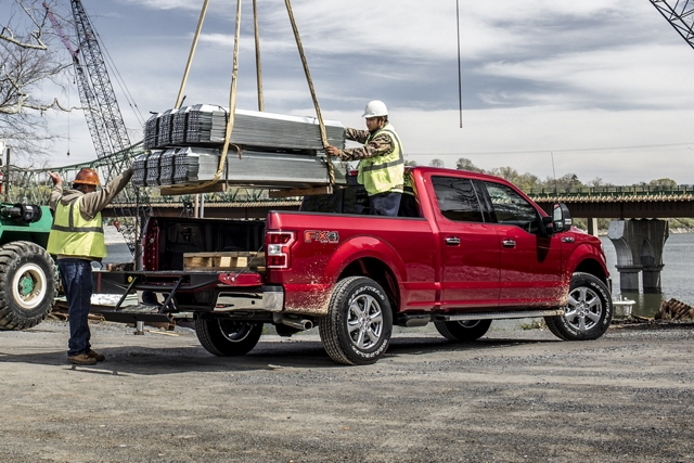 Workers putting heavy load into pickup bed of 2020 Ford F 1 50