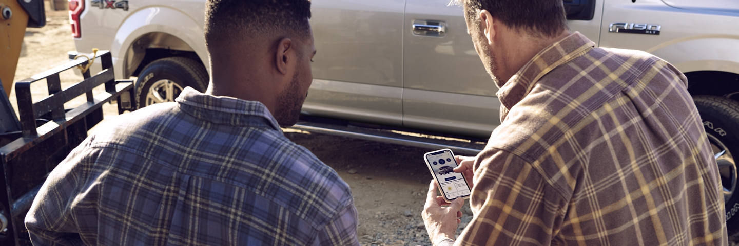 Two men on a worksite interact with the FordPass App in front of a 2020 Ford F 1 50 pickup truck