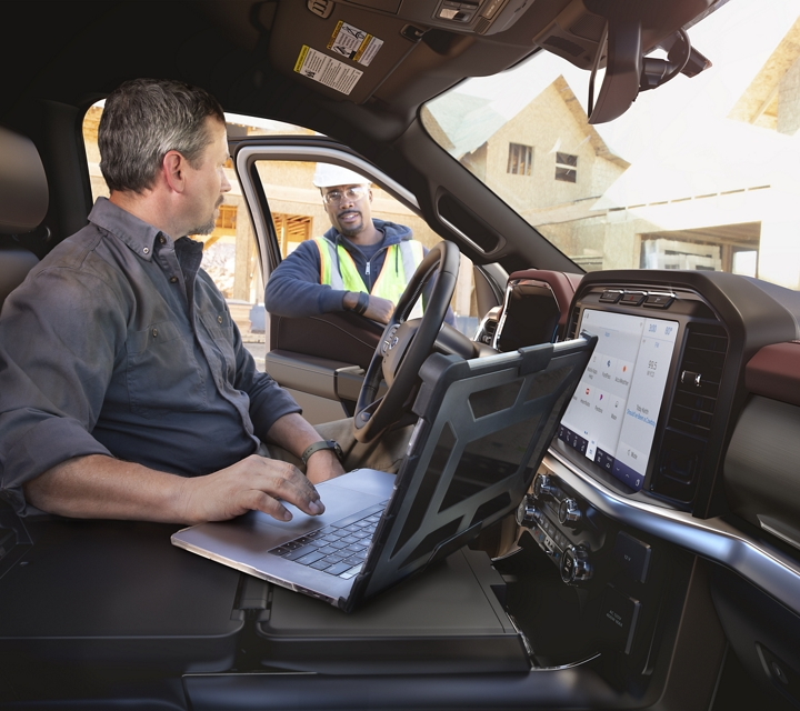 A man using a laptop on the center console worktable in a 2021 Ford F one fifty