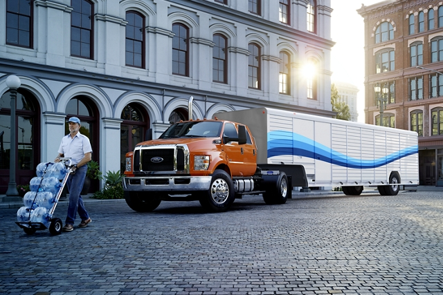 Worker unloading water from 2021 Ford F 7 50 Regular Cab with refrigerated beverage truck upfit and Absopure custom design on city street