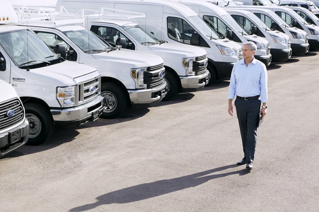 Man walking through lot of white Ford commercial vehicles