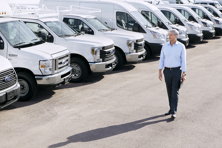 Un hombre camina entre un lote de vehículos comerciales de Ford enWhite