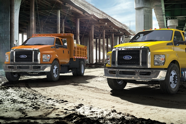 2021 Ford F 7 50 SuperCab in Tangier Orange and 2021 Ford F 7 50 Crew Cab in Bold Yellow parked at worksite