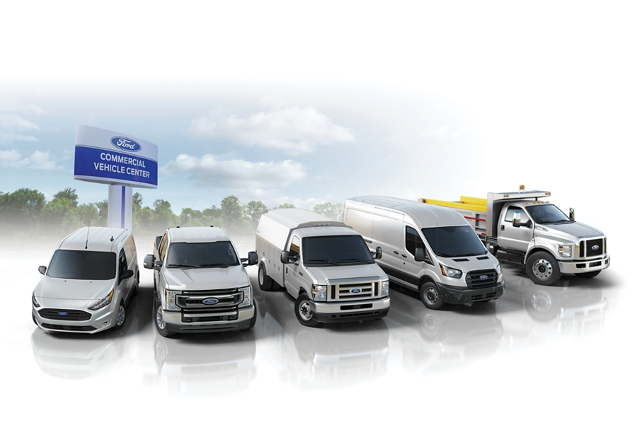 """Varios Vehículos Comerciales Ford estacionados cerca de un letrero que dice """"Commercial Vehicle Center"""""""