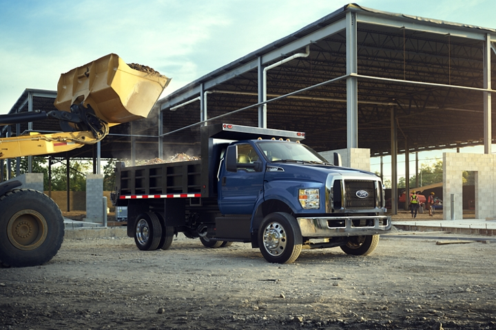 Bulldozer dumping dirt into dump truck upfit of 2021 Ford F 7 50 Regular Cab in Blue Jeans
