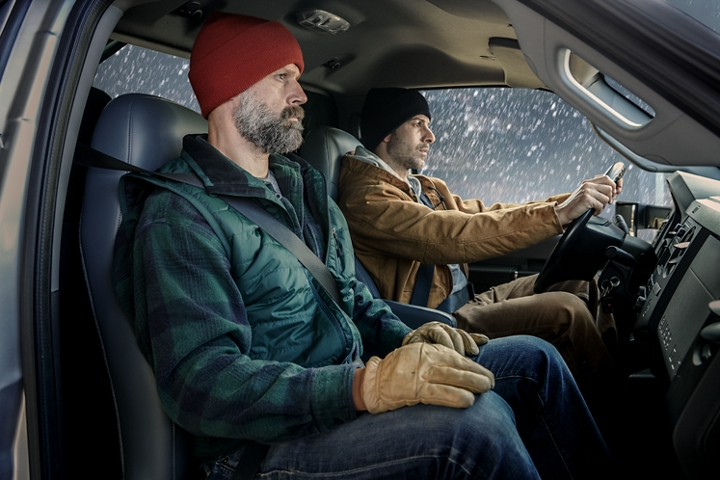 Driver and passenger in winter clothing in front interior of 2021 Ford F 7 50 Regular Cab