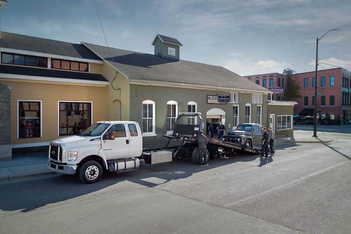 2021 Ford F 6 50 SuperCab with rollback body flatbed with tow truck upfit in Oxford White towing car while parked next to building