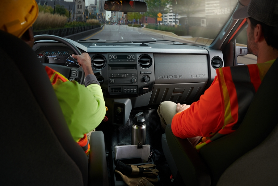 Workers in driver and passenger seats in front interior of 2021 Ford F 7 50