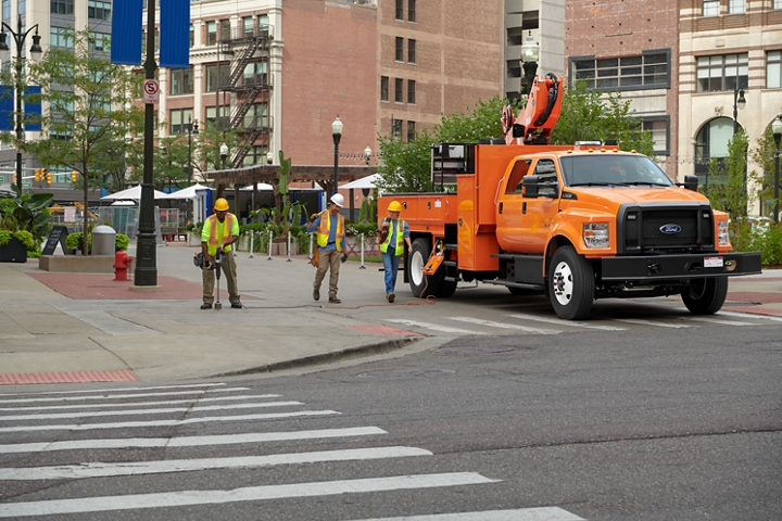 Workers walking near 2021 Ford F 7 50 Crew Cab with aerial lift upfit in Tangier Orange parked on city street