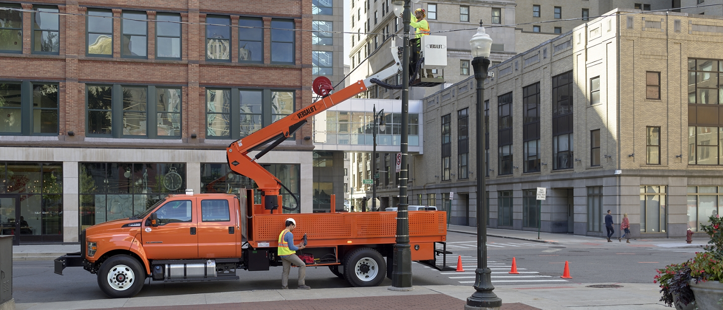 Worker fixing streetlight on city street while inside aerial lift upfit on 2021 Ford F 7 50 Crew Cab in Tangier Orange