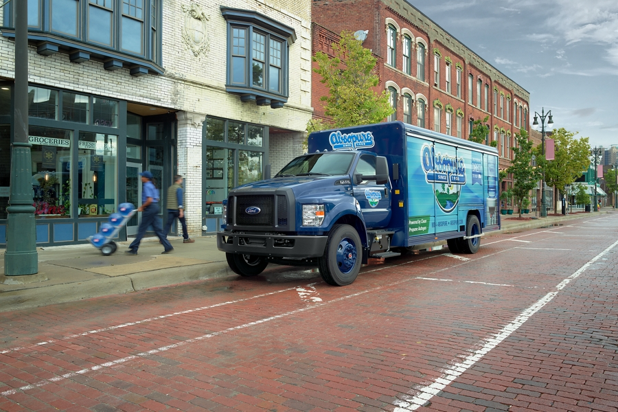 Woman unloading water from 2021 Ford F 7 50 with Absopure branding parked on brick road in city