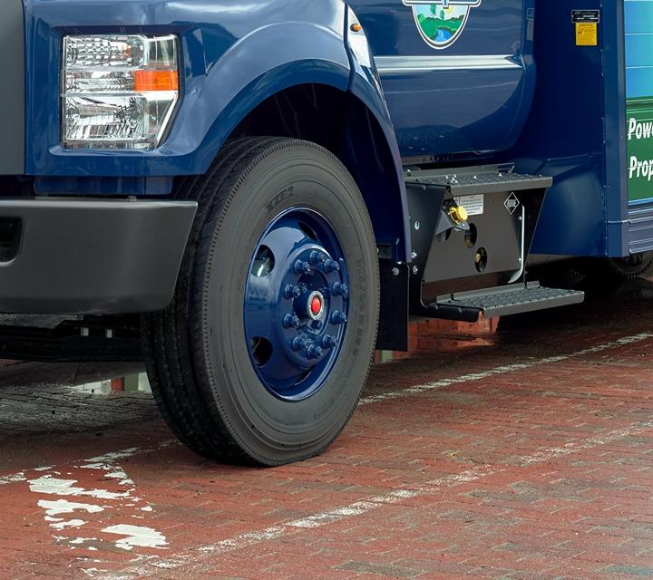Un trabajador descarga agua de unaFordF750Regular Cab2021 con mejora para bebidas refrigeradas y diseño personalizado de Absopure en una calle de ciudad