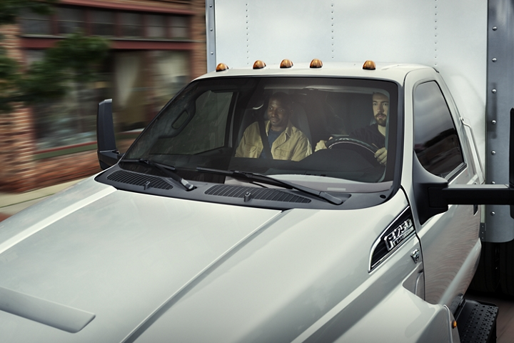 Close up on driver and passenger behind front windshield of 2021 Ford F 7 50 Regular Cab with box truck upfit in Iconic Silver
