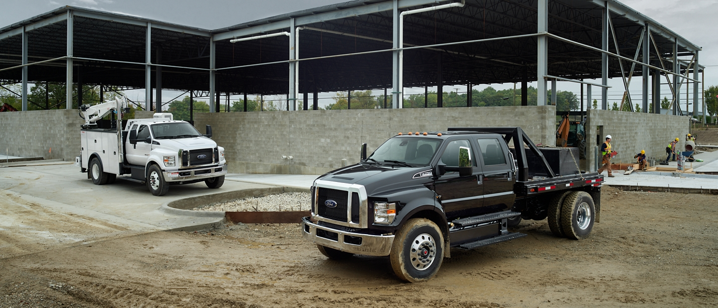 Two 2021 Ford Medium Duty Models in Shadow Black and Agate White parked at worksite