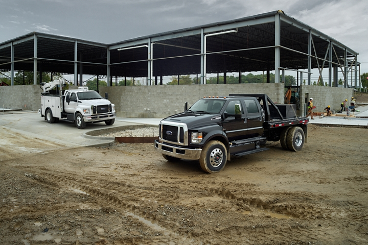 2021 Ford F 7 50 SuperCab in Oxford White and 2021 Ford F 7 50 Crew Cab in Shadow Black parked at construction site