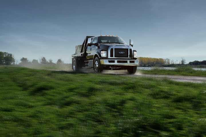 2021 Ford F 7 50 with Utility Stake Bed Upfit in Shadow Black being driven on dirt road near grass and water