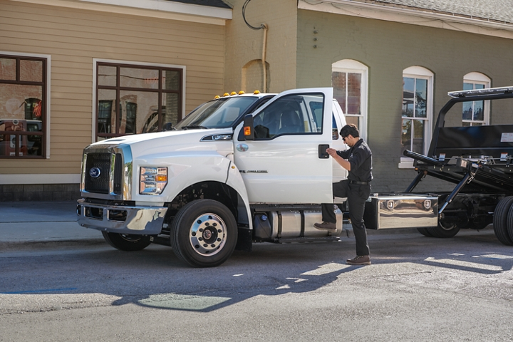 Man entering driver's side door of 2021 Ford F 6 50 SuperCab with rollback body flat bed and tow truck in Oxford White parked next to building
