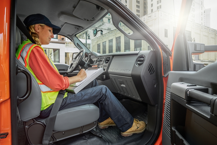 Female worker writing on clipboard in passenger seat of 2021 Ford F 7 50 Crew Cab in Tangier Orange with open passenger side door