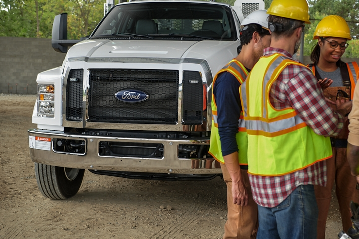 Workers gathered in front of 2021 Ford F 7 50 SuperCab with mechanic truck upfit in Oxford White