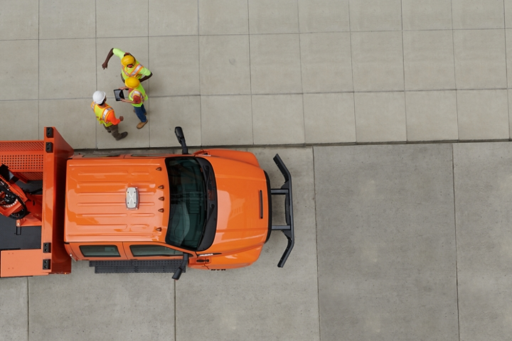 Aerial view of workers next to 2021 Ford F 7 50 Crew Cab with aerial lift upfit in Tangier Orange