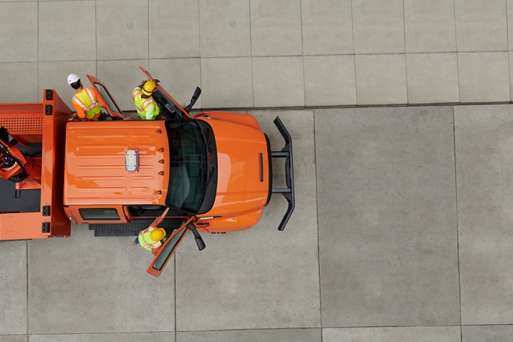 Aerial view of workers exiting 2021 Ford F 7 50 Crew Cab with aerial lift upfit in Tangier Orange