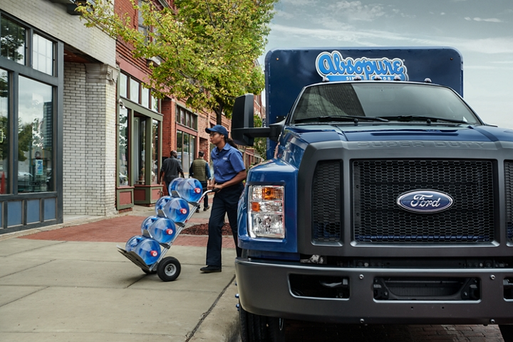 Close up on worker unloading water from 2021 Ford F 7 50 Regular Cab with refrigerated beverage truck upfit and Absopure custom design on city street