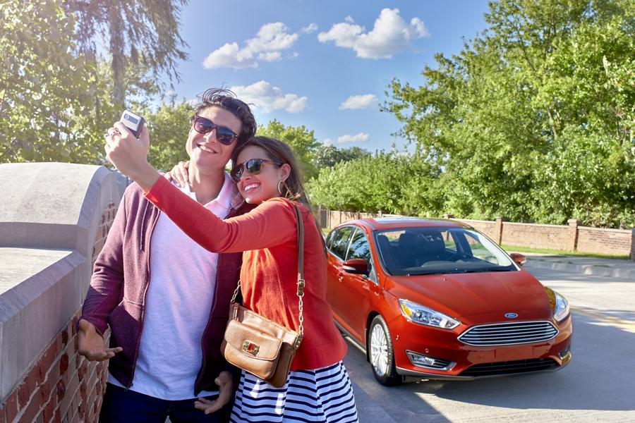 Pareja tomando fotos en frente de un Ford Focus 2018 estacionado