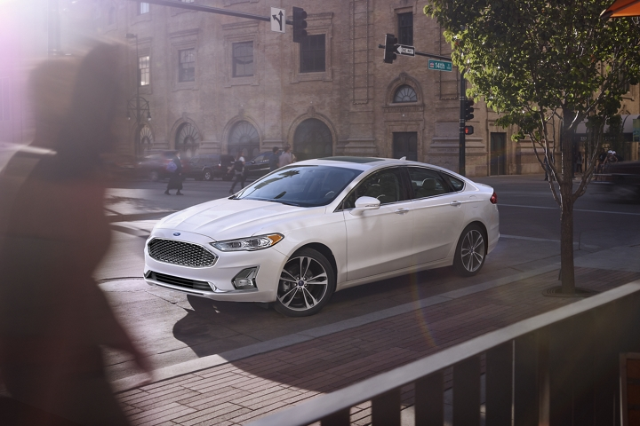 2020 Ford Fusion Titanium shown in White Platinum Metallic with standard wheels being driven down a street with a lot of pedestrians