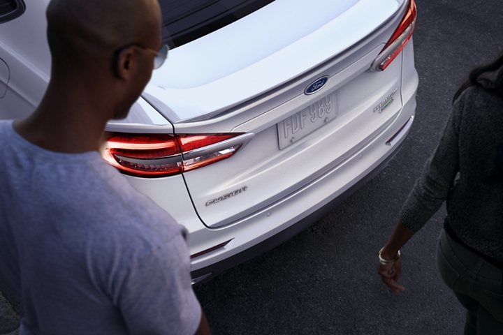 A person looking at the 2020 Ford Fusion Titanium shown in White Platinum Metallic with rear spoiler