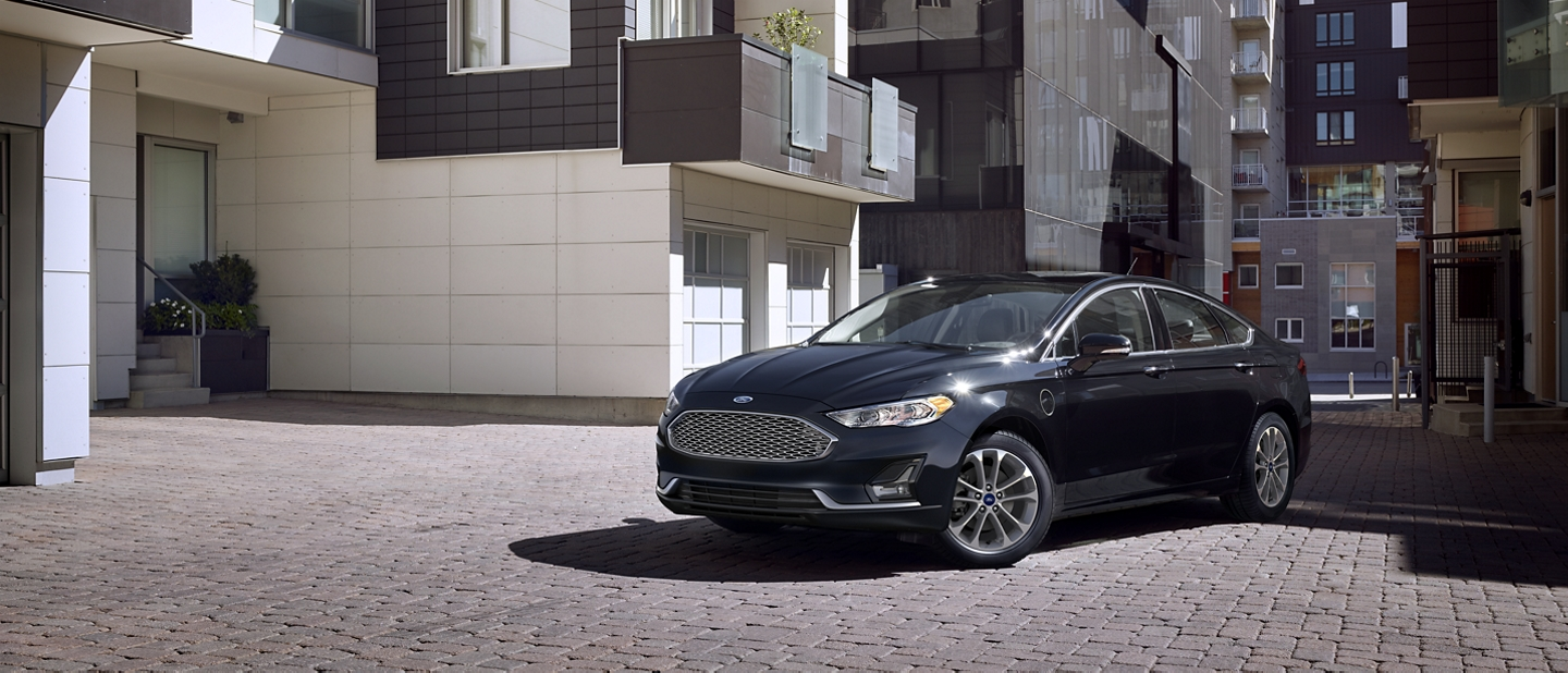 A 2020 Ford Fusion Plug in Hybrid parked in front of an apartment complex