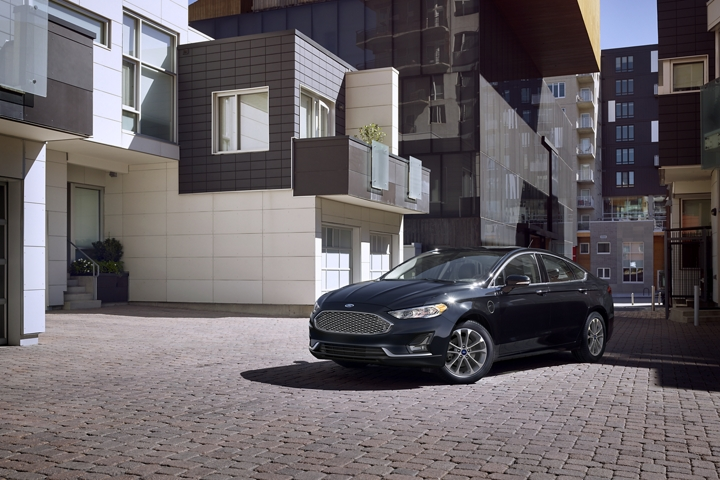2020 Ford Fusion Plug in Hybrid Titanium in agate black parked in front of a modern apartment complex