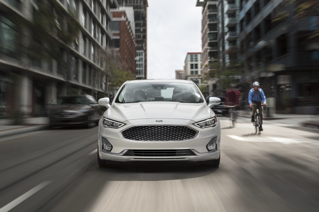 A 2020 Ford Fusion Hybrid with eco select and eco cruise being driven past two bikers on the side of the road