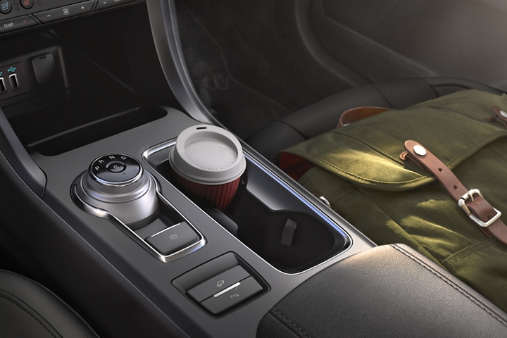 2020 Ford Fusion Titanium interior with rotary gear shift dial positioned next to a cupholder with a cup of coffee