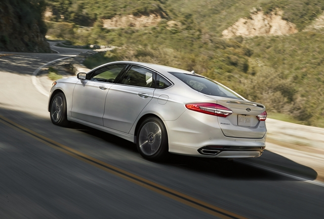 A 2020 Ford Fusion in Oxford White being driven around a bend