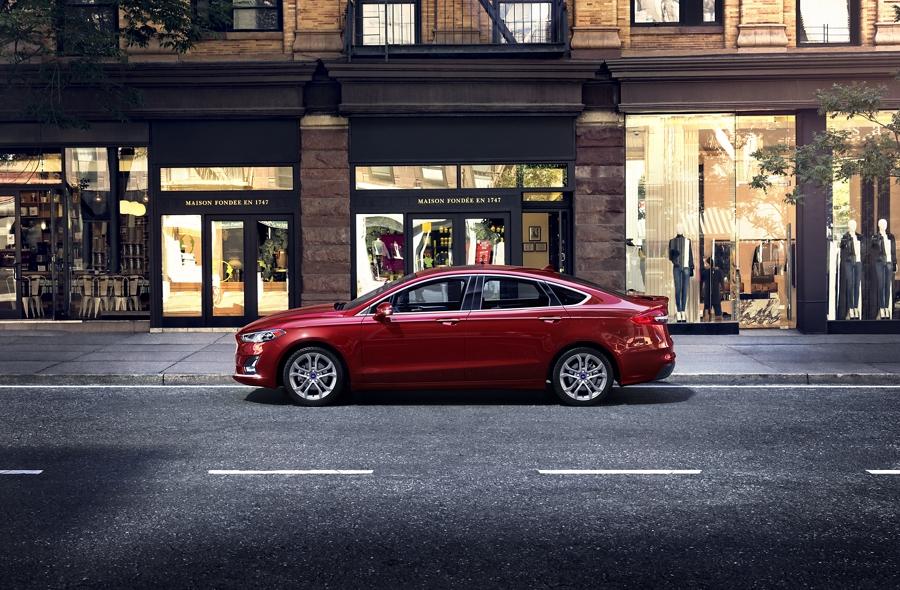 Un Ford Fusion Hybrid 2020 en Rapid Red andando por una calle de la ciudad