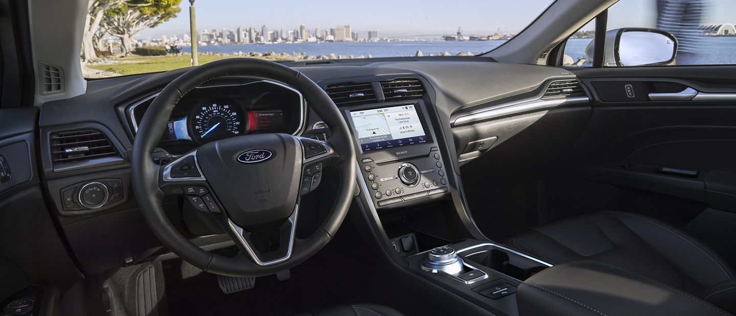 Behind the wheel of the 2020 Ford Fusion looking out at a body of water with a city scape in the background