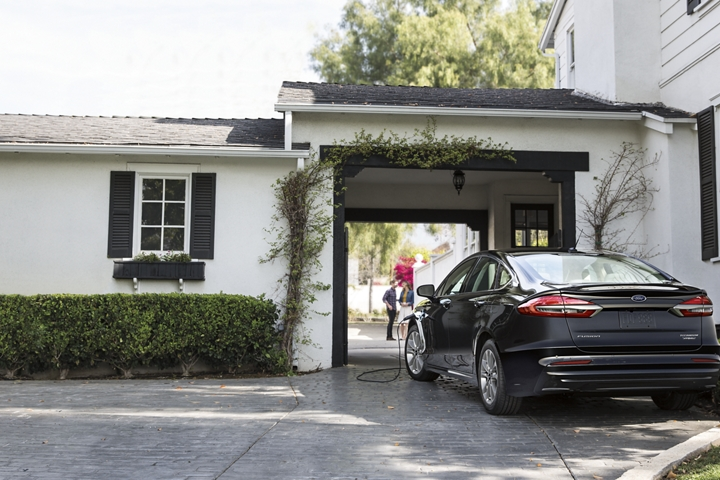2020 Ford Fusion Plug in Hybrid Titanium shown in Agate Black being charged in a garage