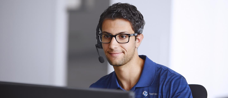Hombre usando un auricular con micrófono sentado enfrente de la pantalla de una computadora