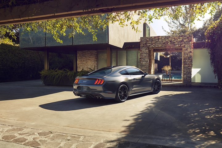 Rear side image of the 2020 Ford Mustang parked in front of a modern home
