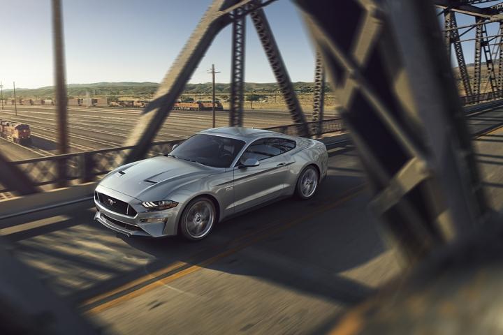 Ford Mustang G T 2020 en Iconic Silver cruzando un puente de metal sobre un patio de maniobras.