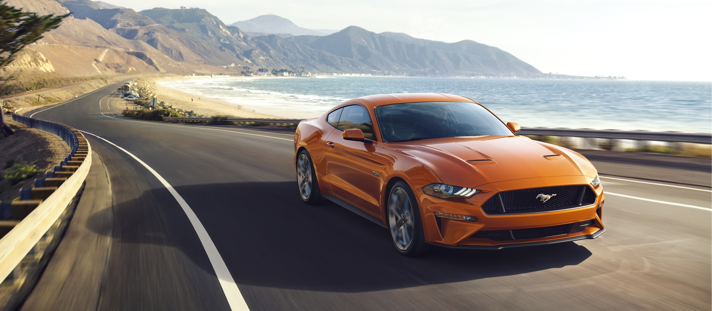 2020 Ford Mustang in twister orange driving on the coast beside the ocean