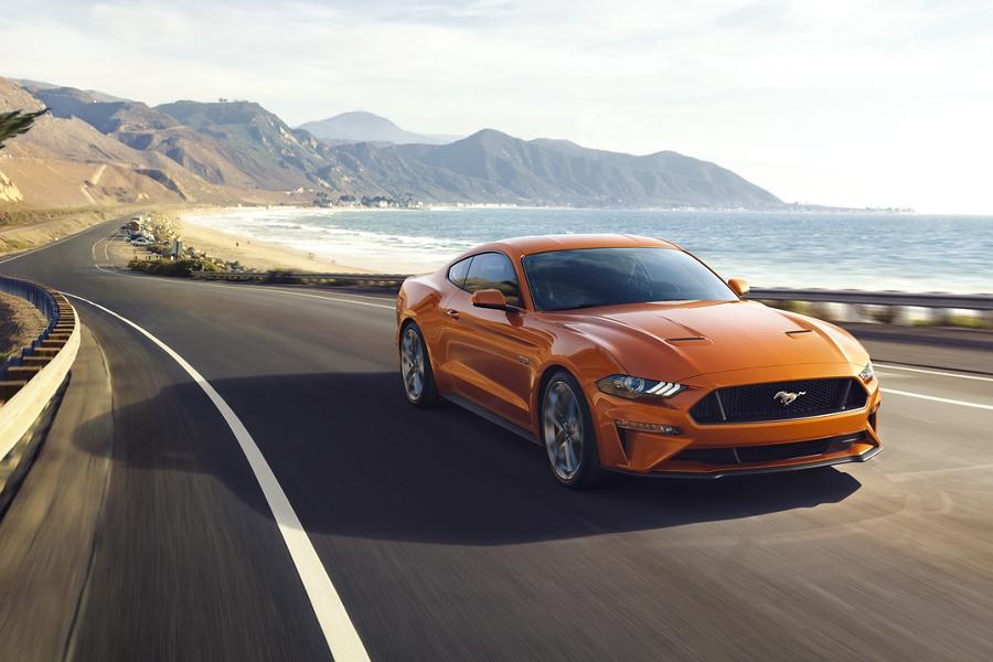 Ford Mustang 2020 en Twister Orange andando por la costa al lado del océano